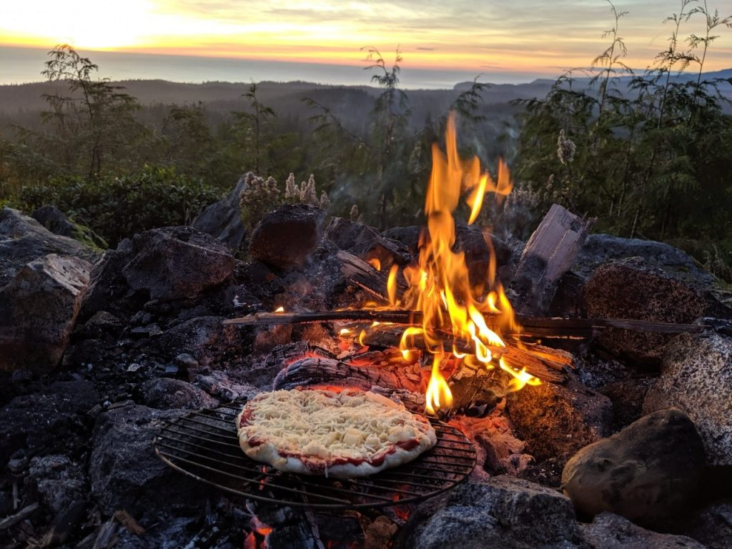 Homemade tomato and cheese pizza set on grill next to campfire with forest and ocean backgound