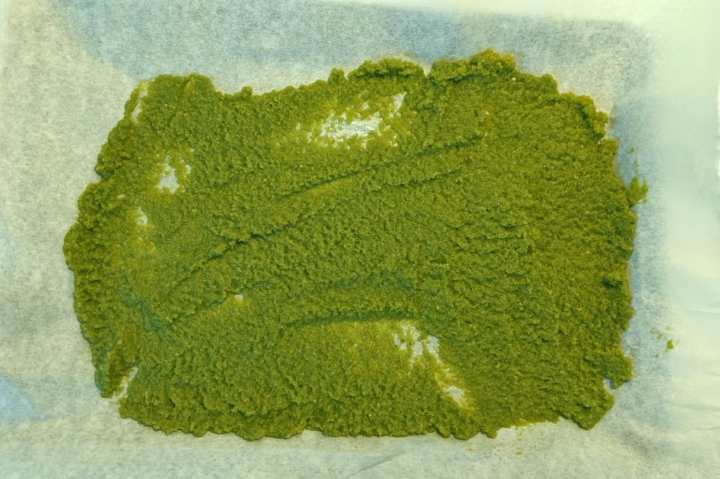 Blended Thai Green Curry paste mixture spread onto parchment paper on baking tray