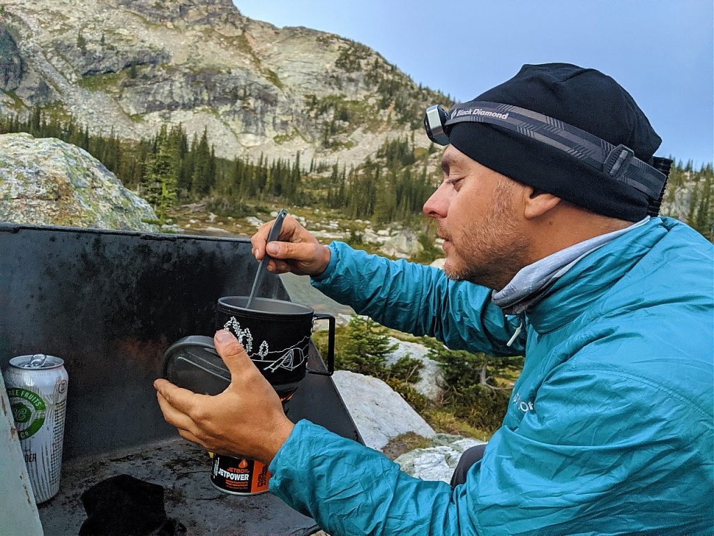 JR looking at contents of backpacking stove post with mountainous backdrop