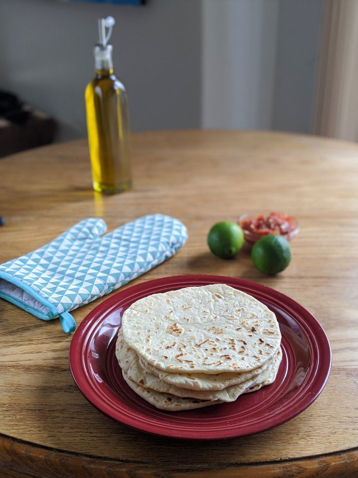 Stack of flour tortilla on a red plate