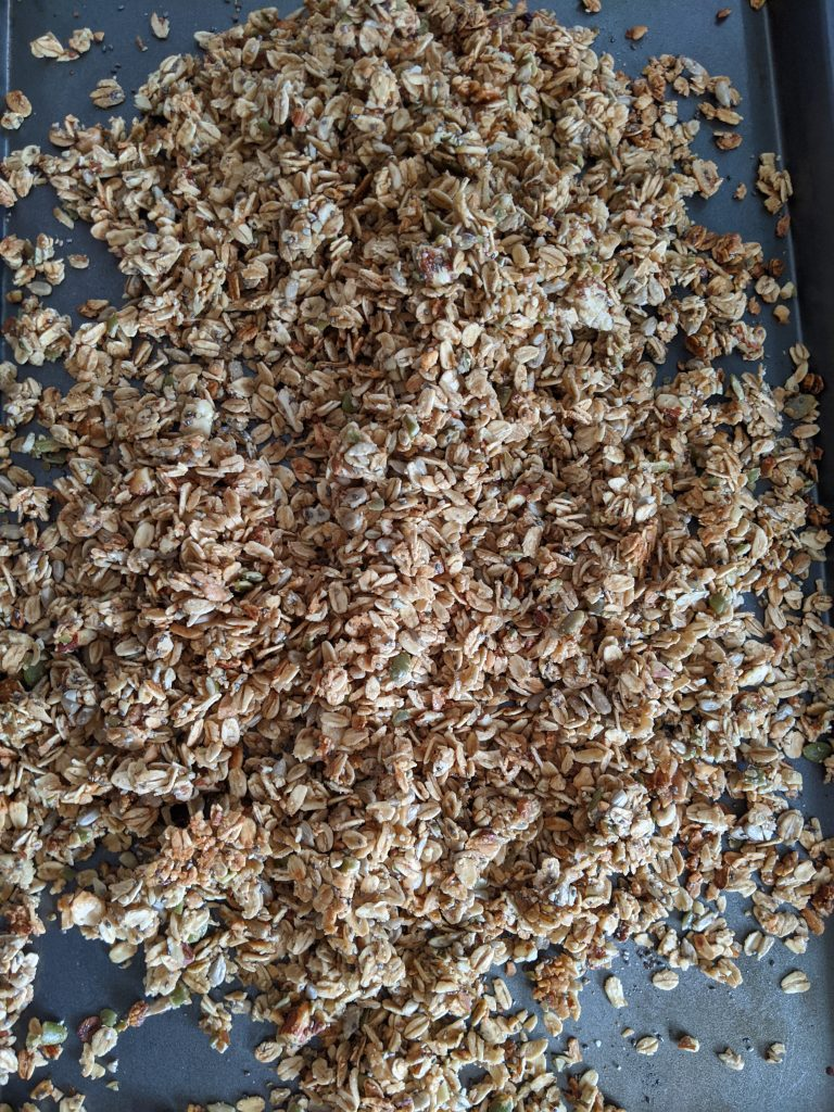The cooked Wholesome Maple Nut Breakfast Granola cooling on a baking tray