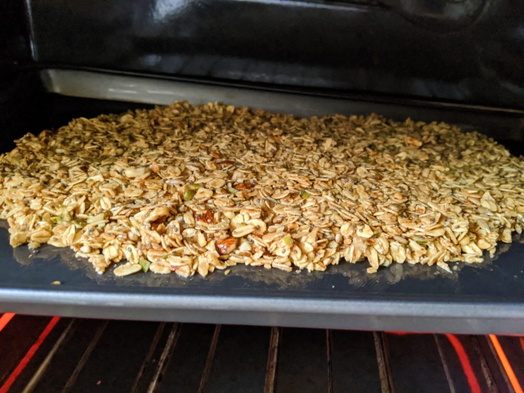 The finished Wholesome Maple Nut Breakfast Granola spread onto a baking tray and in the oven
