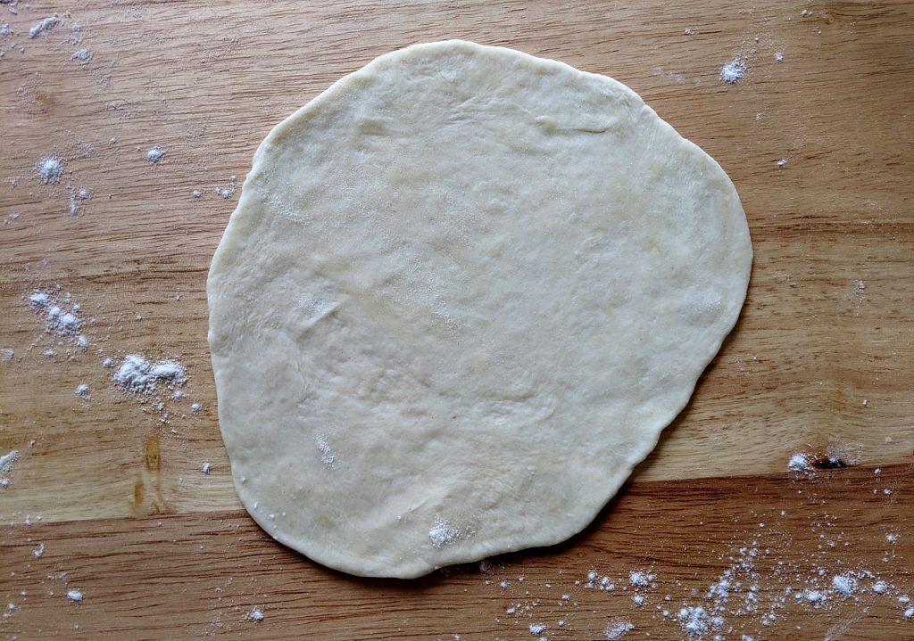 A fully flattened piece of homemade tortilla dough