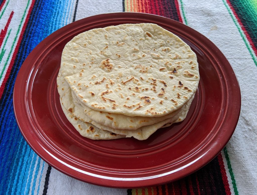 Stack of homemade flour camping tortillas on red plate