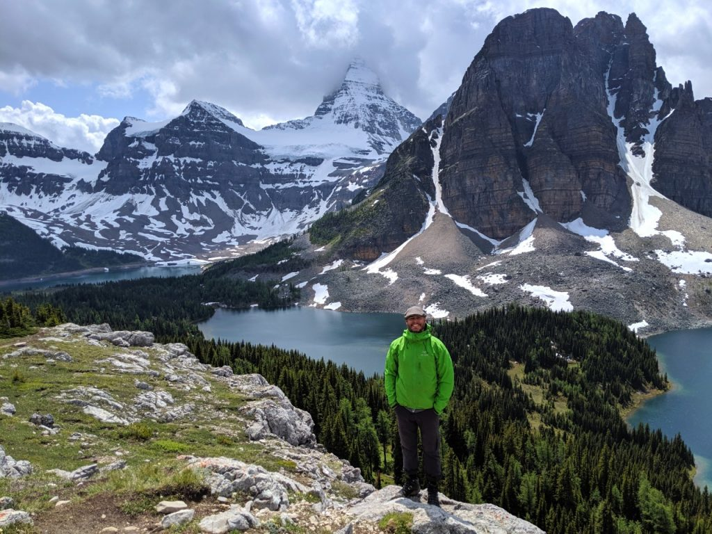 JR standing and looking at camera, with backdrop of alpine lakes and snow capped mountains in Mount Assiniboine Provincial Park, British Columbia, Canada