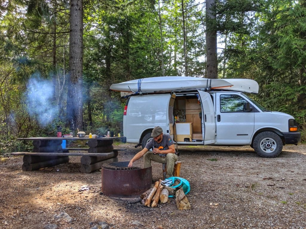 JR sitting at campfire in front of white van with open door, while camping in British Columbia