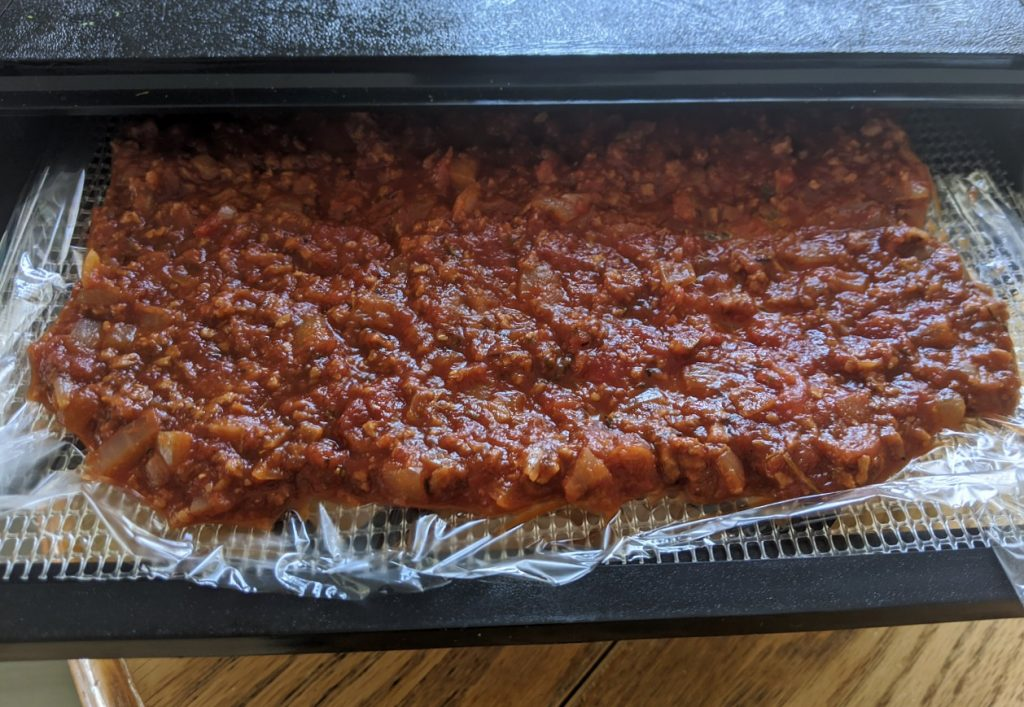 Dehydrator tray covered with wax paper and veggie bolognese sauce, ready to dehydrate