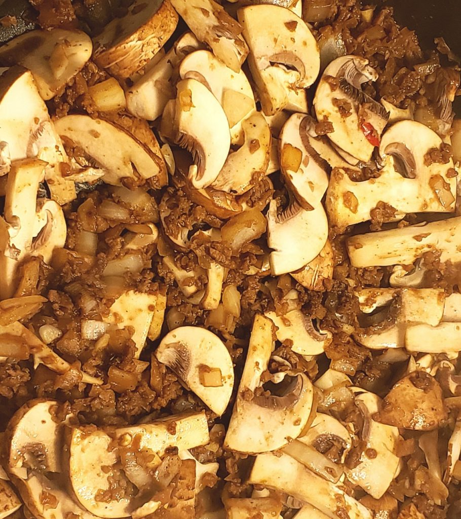 Close up of mushrooms, TVP, onions and garlic cooking in a pan