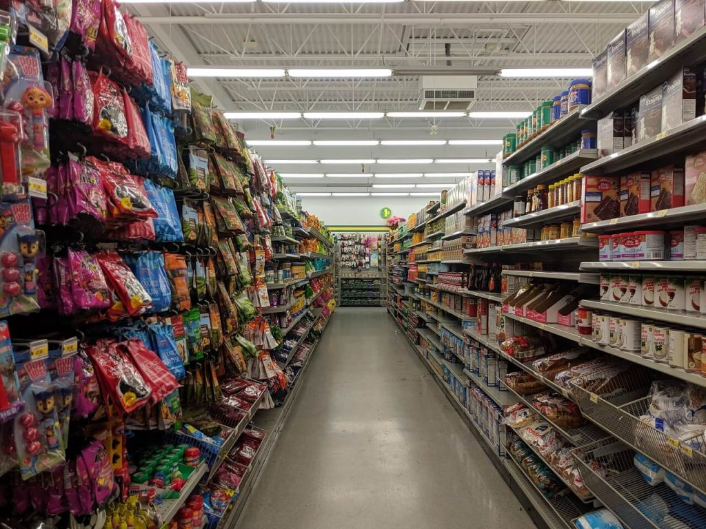 Looking down an aisle at a dollar store, with food on shelves on each side, with view of high ceiling above