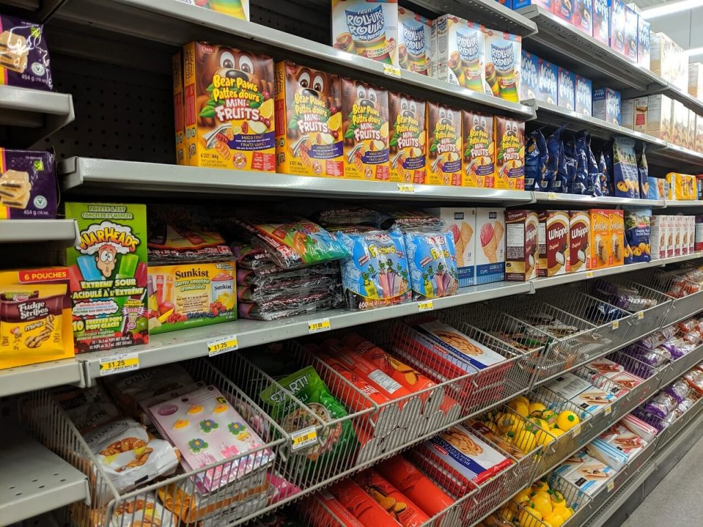 Side view of cookie aisle at dollar store, with different packets of cookies on shelves