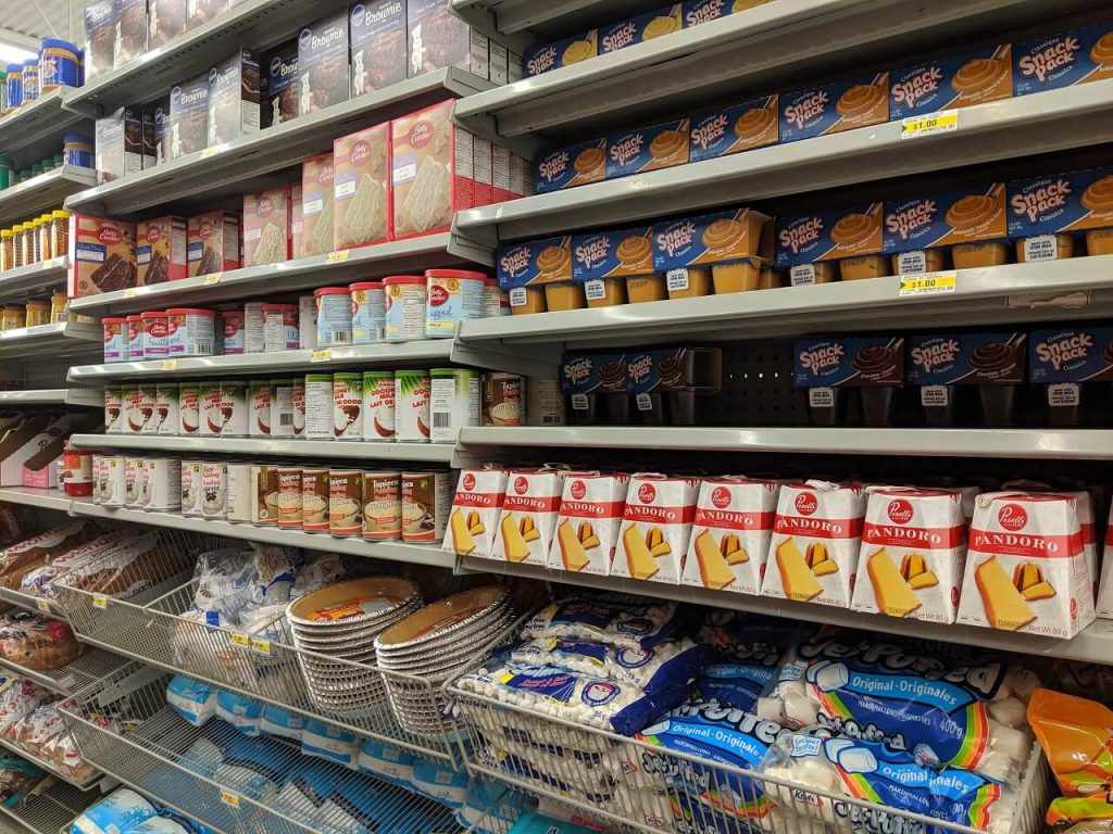 Side view of shelves in dollar store, with baking items like icing and sugar