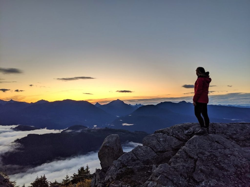 Gemma is standing on a rock on the right hand side of the photo, looking at the sunrise behind mountains below